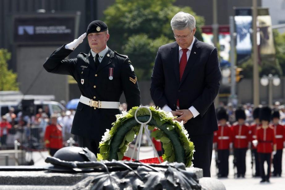 Le premier ministre Harper se recueille devant le... (PHOTO CHRIS WATTIE, REUTERS)