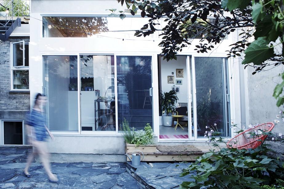 Tel un bloc blanc, le rajout, qui accueille un espace de travail agréable, s'ouvre généreusement sur le jardin. D'où cette sensation de vivre dehors. Observez la façade: des panneaux d'aluminium blanc participent à l'équilibre de la composition des surfaces vitrées.<!--EndFragment--> (PHOTO MATHIEU LAVERDIÈRE, FOURNIE PAR APPAREIL ARCHITECTURE)