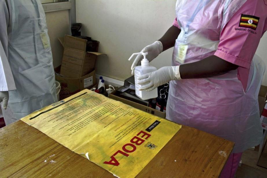Le personnel médical désinfecte une table à l'aéroport... (PHOTO ISAAC KASAMANI, AFP)
