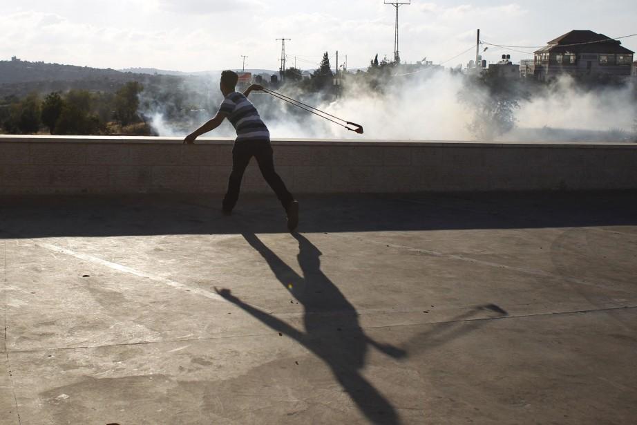 Un jeune palestinien lance des pierres en direction... (Photo Mohamad Torokman, Reuters)