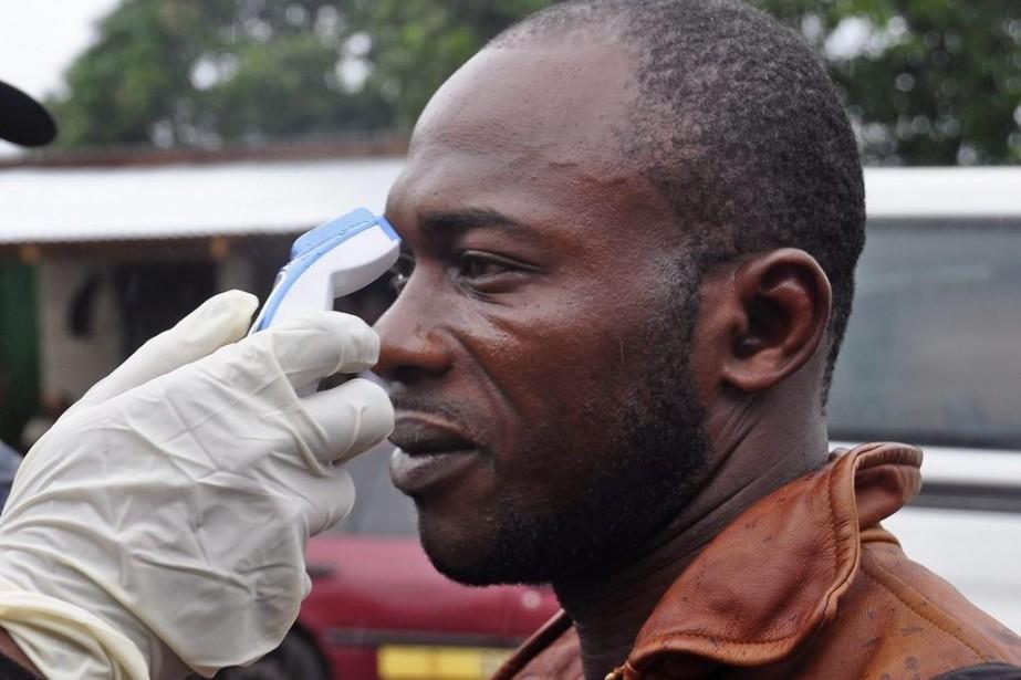 Un homme doit faire prendre sa température avant... (PHOTO ABBAS MOMANI, AFP)