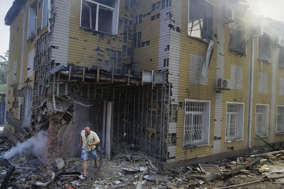 Un homme sort en courant d'un bâtiment détruit... (PHOTO SERGEI GRITS, AP)