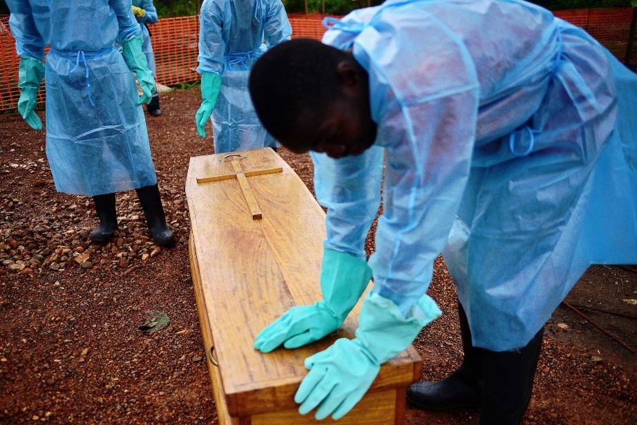 Des employés du gouvernement du Sierra Leone enterrent... (Photo Carl de Souza, AFP)