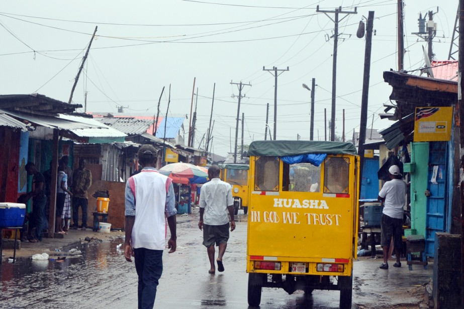 Des gens marchent sous la pluie à West... (PHOTO ZOOM DOSSO, ARCHIVES AFP)