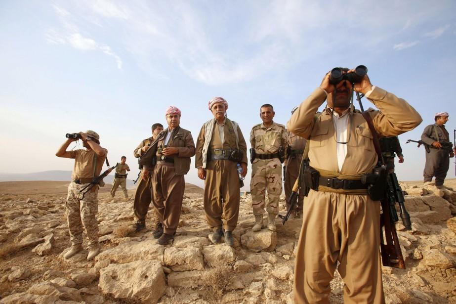 Des combattants kurdes montent la garde au sud... (PHOTO YOUSSEF BOUDLAL, REUTERS)