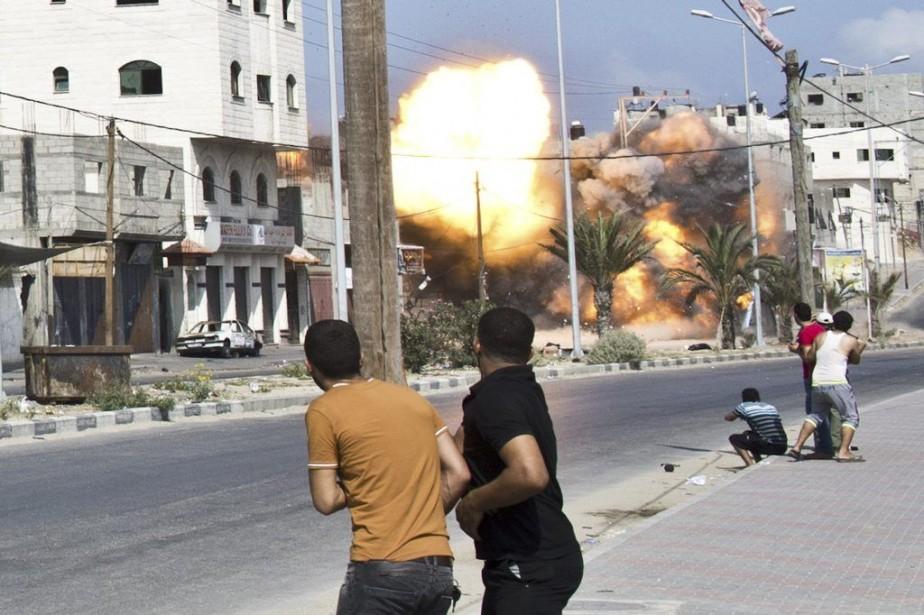 Des Palestiniens voient une bombe exploser sur une... (PHOTO ROBERTO SCHMIDT, AFP)