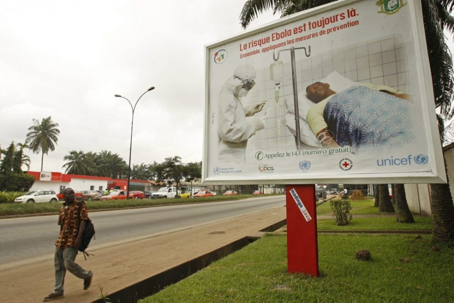 Un homme passe devant un panneau publicitairede la... (PHOTO SEVI HERVE GBEKIDE, AP)