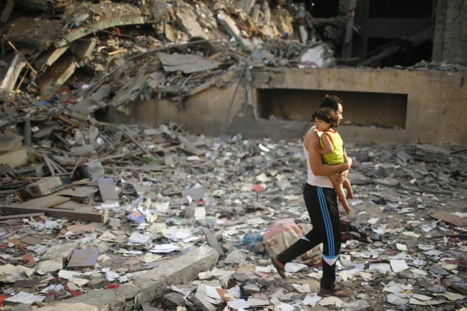 Un homme, son enfant dans les bras, marche... (PHOTO MOHAMMED SALEM, REUTERS)