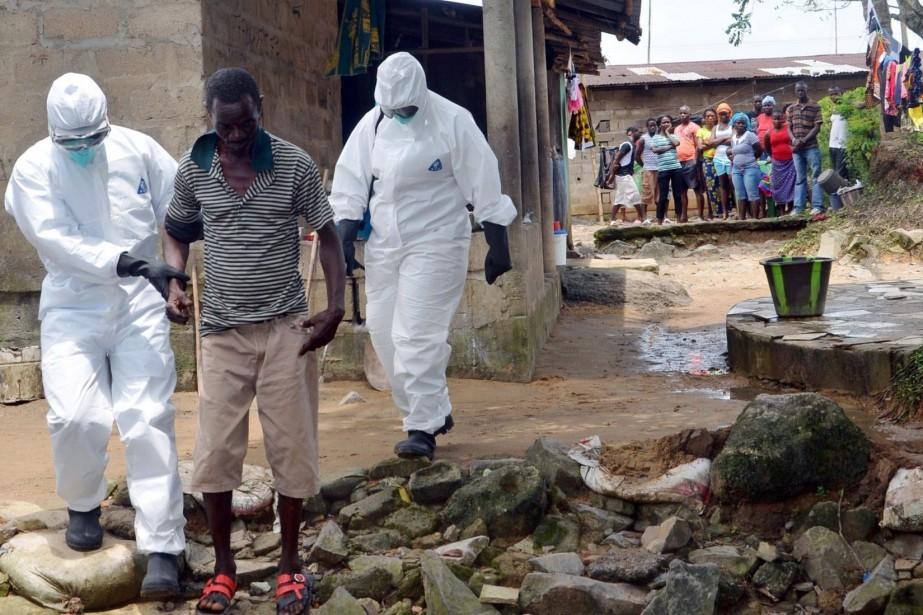 Des infirmiers escortent un malade infecté par le... (Photo ZOOM DOSSO, AFP)