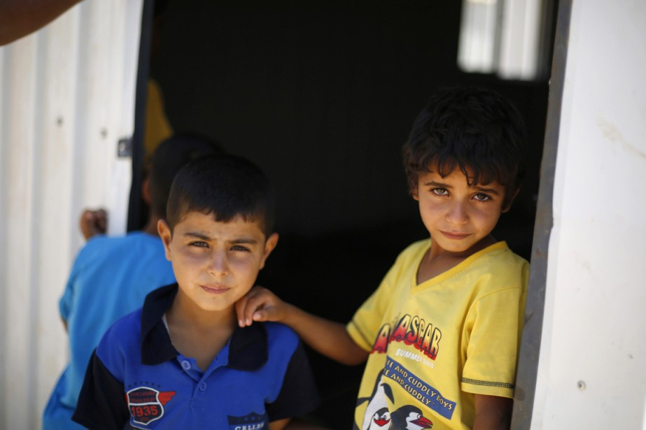 Deux jeunes Syriens sont photographiés dans le camp... (PHOTO MUHAMMAD HAMED, ARCHIVES REUTERS)