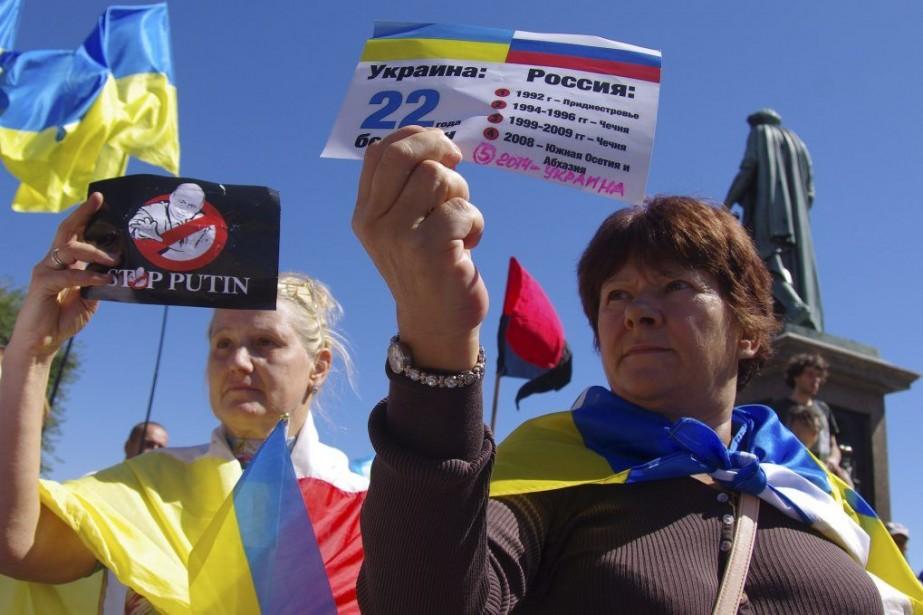 Des femmes tiennent des brochures où il est... (PHOTO ALEXEY KRAVTSOV, AFP)