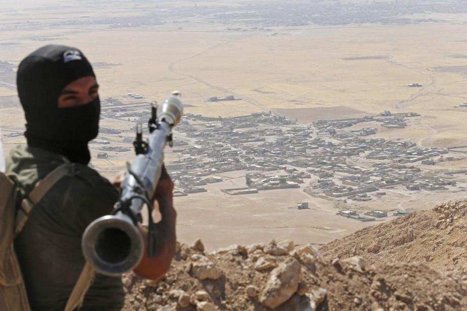Un combattant kurde armé d'un lance-roquette surplombe le... (PHOTO AHMED JADALLAH, ARCHIVES AFP)