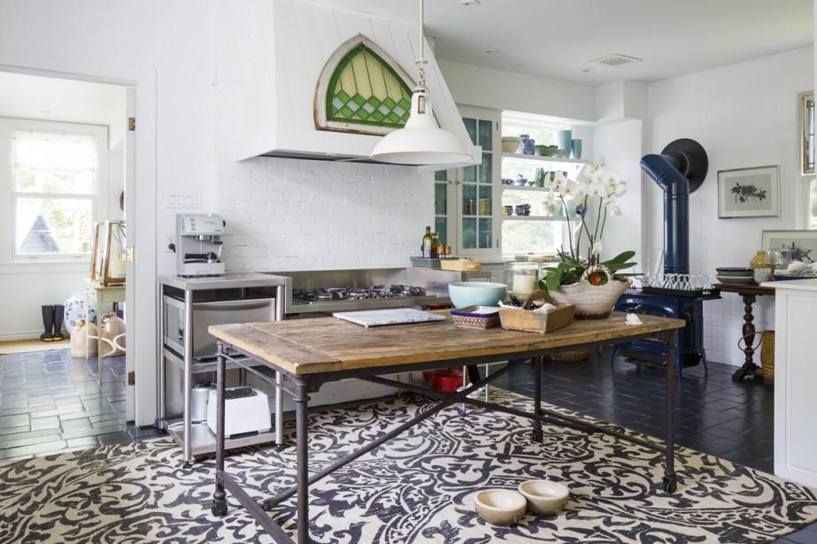 Les propriétaires actuels n'ont apporté que très peu de changements à la cuisine. Ils ont repeint le carrelage en bleu, les armoires en blanc et ajouté leurs touches personnelles. La table sert d'îlot et de surface de travail. (PHOTO ULYSSE LEMERISE, COLLABORATION SPÉCIALE)