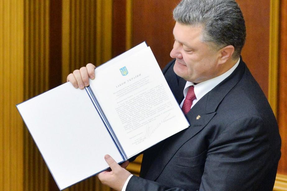 Le président Petro Porochenko brandit fièrement l'accord d'association... (PHOTO GENYA SAVILOV, AFP)