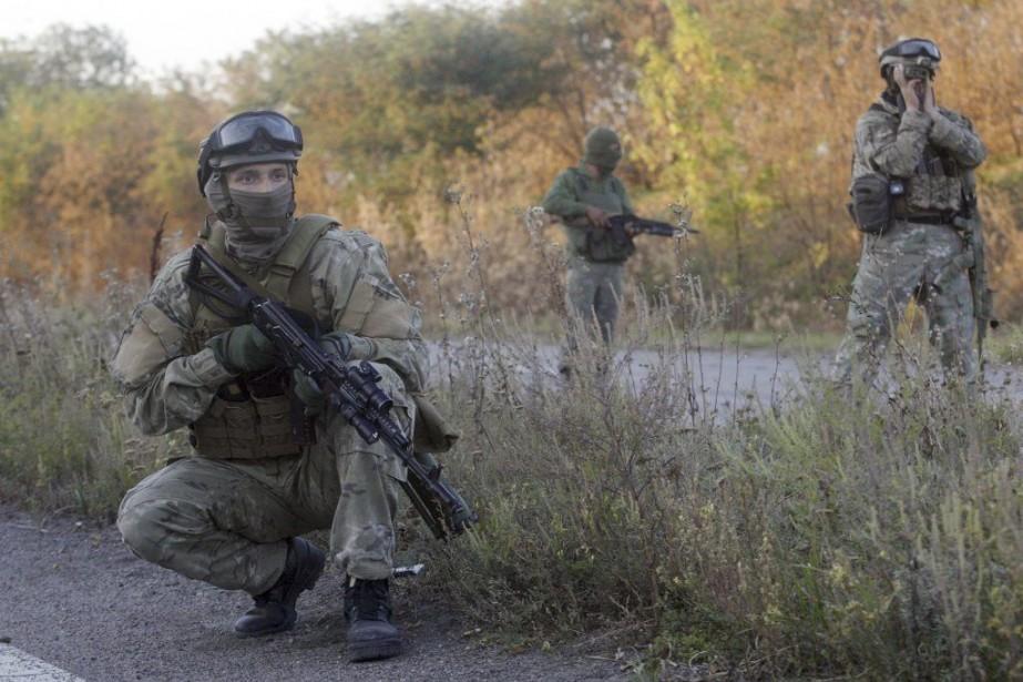 Des soldats ukrainiens patrouillent sur une route près... (Photo ANATOLII STEPANOV, AFP)