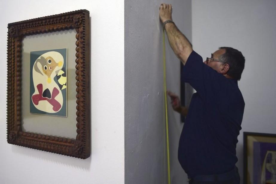 Un employé installe une oeuvre faisant partie de... (Photo: AFP)