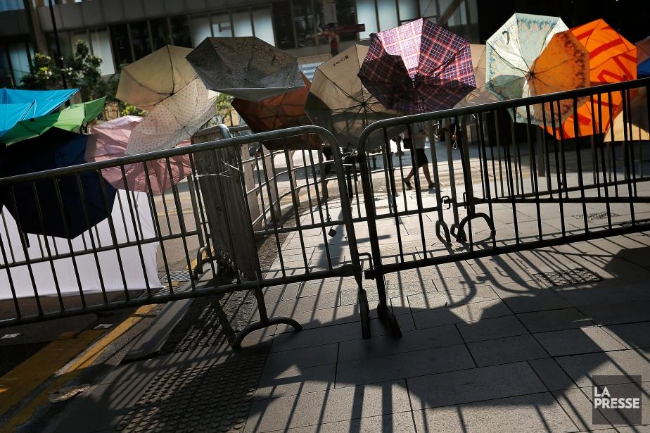 Des parapluies accrochés à des barrières de sécurité symbolisent la révolution en cours à Hong Kong, car ils sont utilisés par les manifestants afin de se protéger des répliques policières. (PHOTO AP)