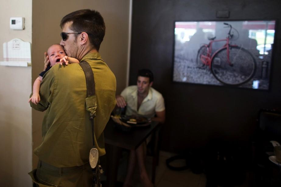 Un soldat israélien embrasse son bébé, dans un... (PHOTO RONEN ZVULUN, ARCHIVES REUTERS)