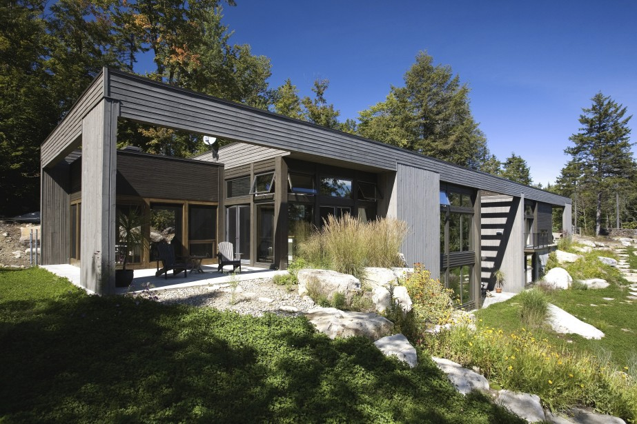 La maison de type longhouse, conçue par l'architecte souvent primé Alain Carle, est recouverte de clins et de planches de bois, avec des fenêtres dont l'extérieur est en alu à cause de l'exposition au sud. Derrière le patio, une pièce fermée par des moustiquaires seulement permet de faire des barbecues à l'année. (PHOTO FOURNIE PAR SOTHEBYS REALTY INTERNATIONAL QUÉBEC)