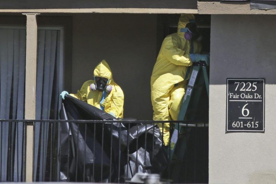 Des nettoyeurs de matières dangereuses installent du matériel... (PHOTO ASSOCIATED PRESS)