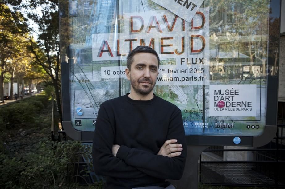 David Altmejd devant une affiche de son exposition...