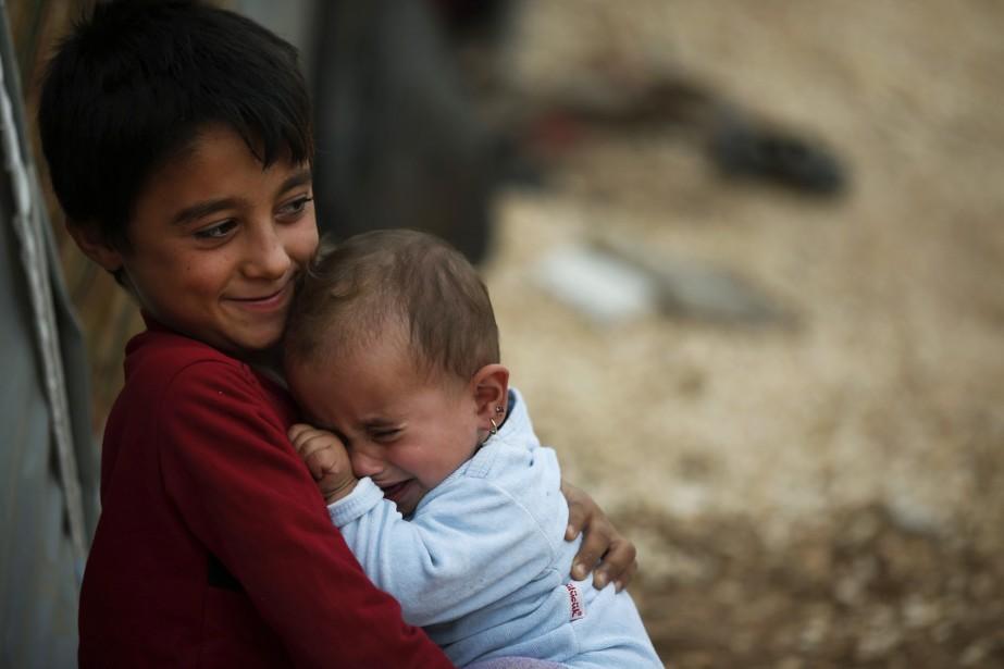 Un jeune garçon kurde console sa sœur dans un camp de réfugiés près de la frontière entre la Turquie et la Syrie. (Associated Press)