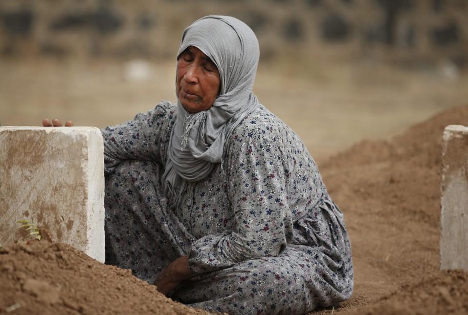 Rabia Ali se recueille àa la tombe de son fils Seydo Mehmud Curo, un combattant kurde tué en combattant l'État islamique dans les environs de Kobané, en Syrie. (Associated Press)