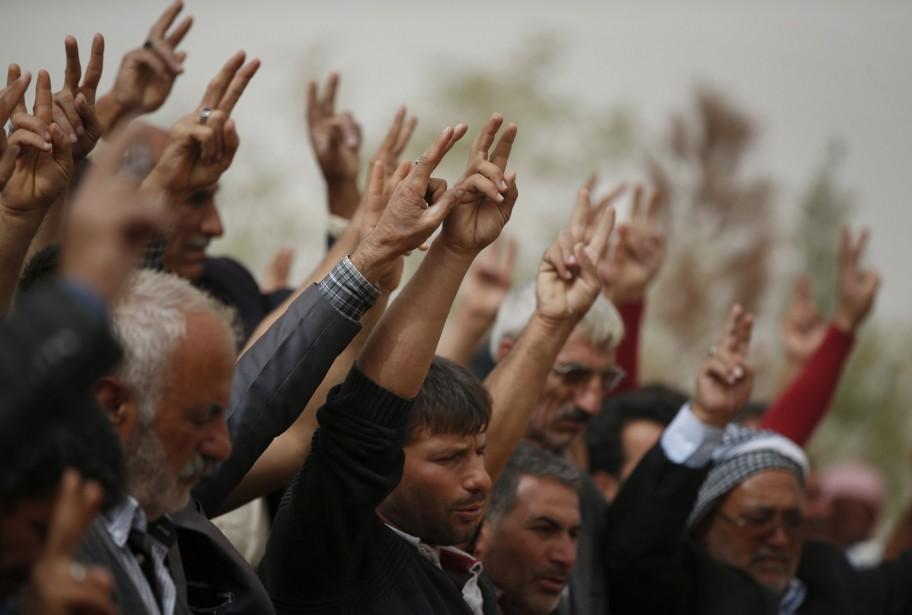 En deuil, des Kurdes chantent et rendent hommage à leurs disparus dans un cimetière près de la frontière. (Associated Press)