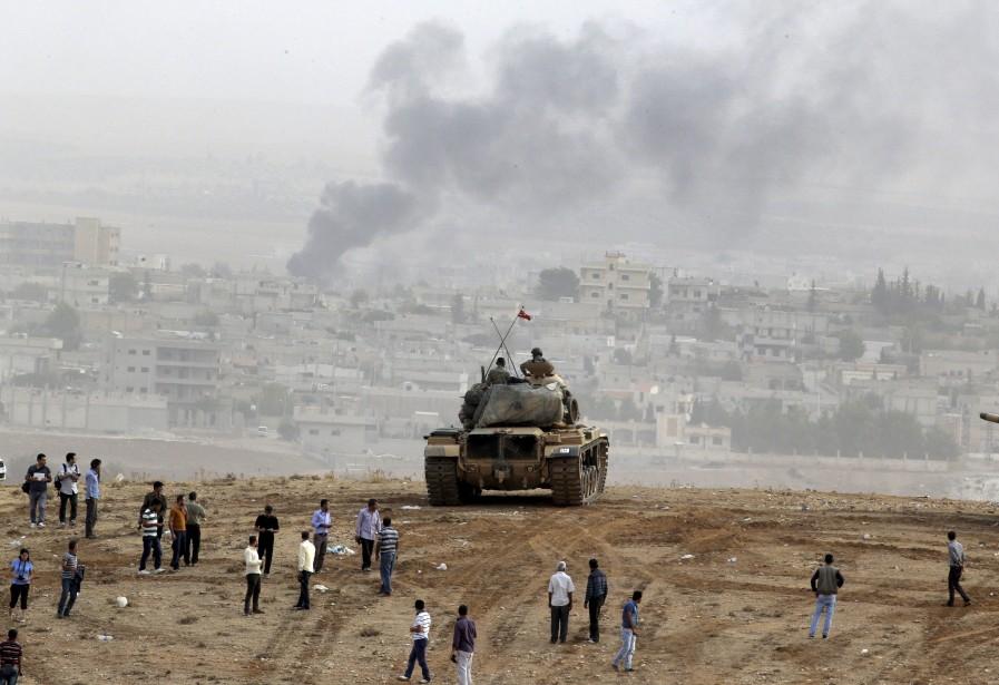 Les gens se rassemblent pour observer les frappes aériennes sur la ville de Kobané. (Associated Press)