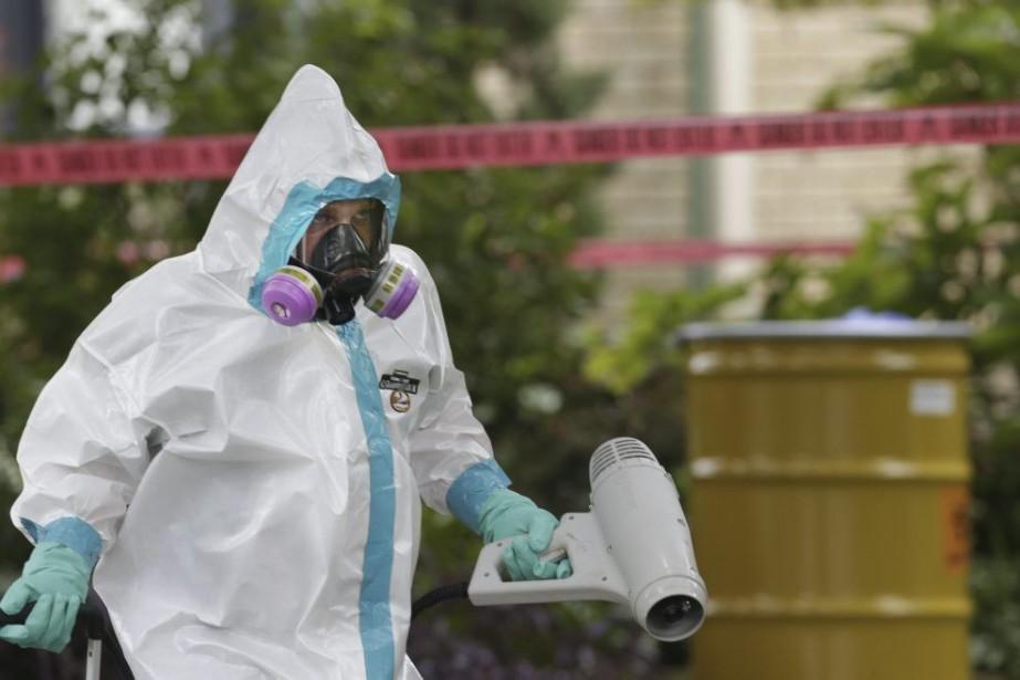 Un employé en combinaison hazmat s'affaire à l'extérieur... (PHOTO LM OTERO, AP)