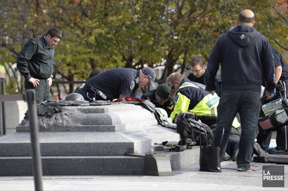 L'intervention de la police et d'ambulanciers devant le... (PHOTO ADRIAN WYLD, LA PRESSE CANADIENNE)