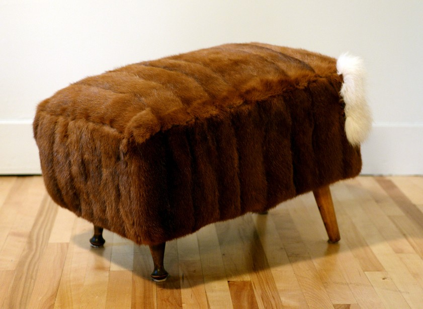 Ce pouf est en vison brun a du style avec son ajout de queue de renard. On remarque qu'il est en angle, pour plus de confort. (Le Solei, Erick Labbé)
