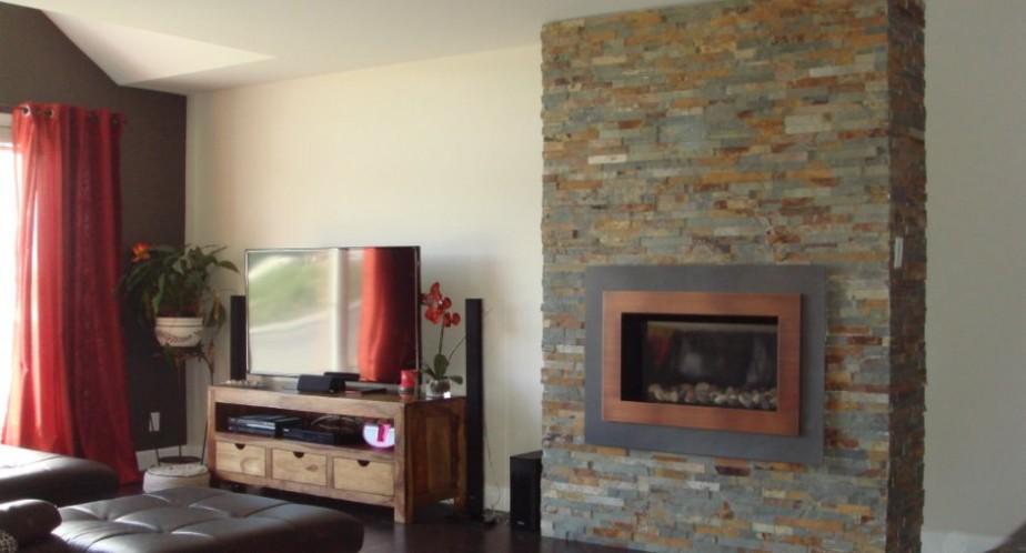 Un foyer au gaz et son manteau en ardoises font figure d'éléments centraux au salon. ()