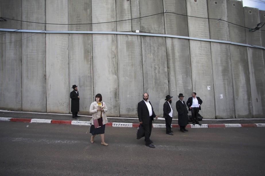 Des membres de la communauté juive ultra-orthodoxe sont vus devant la «barrière de sécurité» construite par Israël, en Cisjordanie, le 4 novembre. (PHOTO Finbarr O'Reilly, ARCHIVES REUTERS)