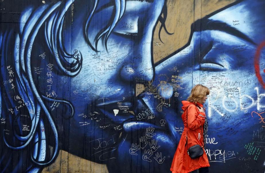 Une femme passe devant un des «murs de la paix» de Belfast, barrières séparant les quartiers catholiques de ceux protestants, le 3 octobre. (PHOTO Cathal McNaughton, ARCHIVES REUTERS)