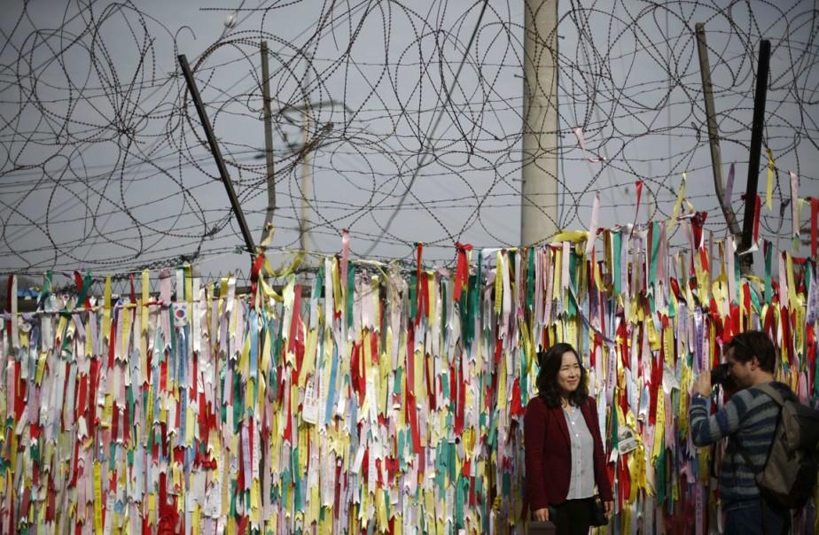 Une barrière surmontée de fils barbelé, décorée de rubans appelant à l'unification des deux Corées, à proximité de la zone démilitarisée séparant la Corée du Nord de celle du Sud depuis l'armistice de 1953. (PHOTO Kim Hong-Ji , ARCHIVES REUTERS)