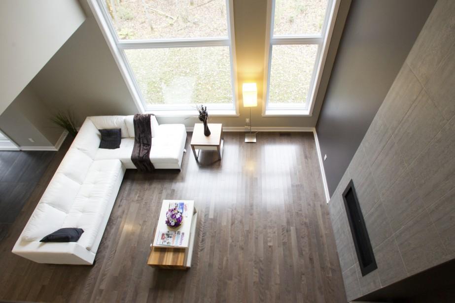 Le salon a un plafond de 18 pieds de hauteur et d'immenses fenêtres afin de mieux admirer le boisé protégé à l'arrière. (Photo Olivier Jean, La Presse)