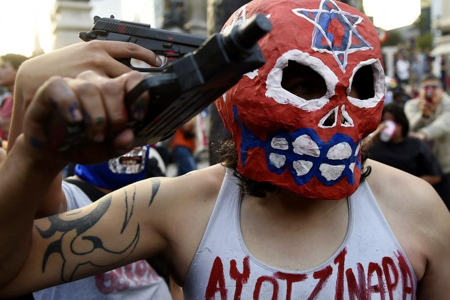 Des étudiants portant un masque de lutteur et... (PHOTO RONALDO SCHEMIDT, ARCHIVES AFP)