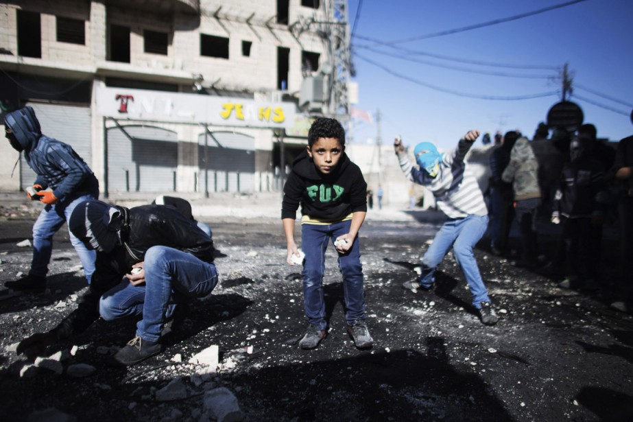 De jeunes garçons palestiniens jettent des pierres en... (PHOTO FINBARR O'REILLY, REUTERS)