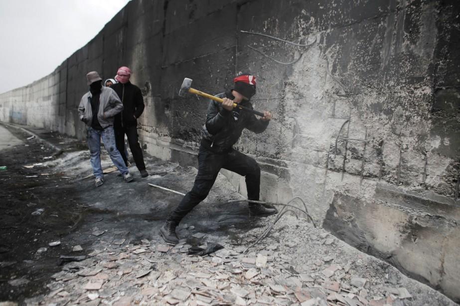 Un activiste palestinien tente de fracasser à coups... (PHOTO AHMAD GHARABLI, AFP)