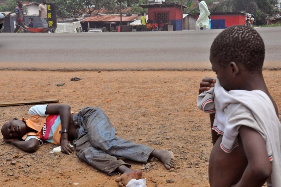 Un jeune garçon se couvre la bouche et... (PHOTO ABBAS DULLEH, ARCHIVES AP)