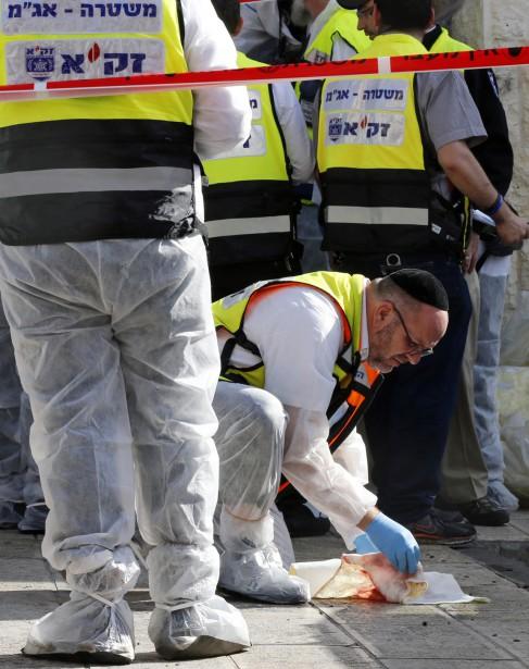 Des employés municipaux ont nettoyé les traces de sangà l'entrée de la synagogue où a été perpétré l'attentat. (PHOTO AMMAR AWAD, REUTERS)