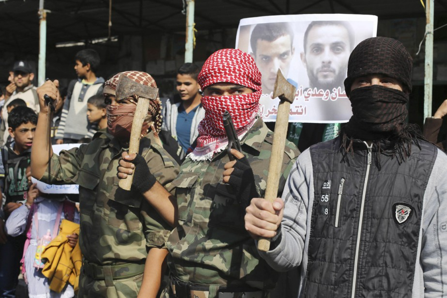 De jeunes Palestiniens ont manifesté leur appui aux deux assaillants en brandissant des haches, nouveau symbole de la résistance armée. (PHOTO IBRAHEEM ABU MUSTAFA, REUTERS)