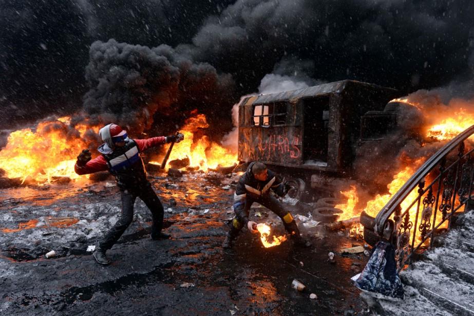 Un militant poro-occidental lance un cocktail Molotov en... (PHOTO VASILY MAXIMOV ARCHIVES AFP)