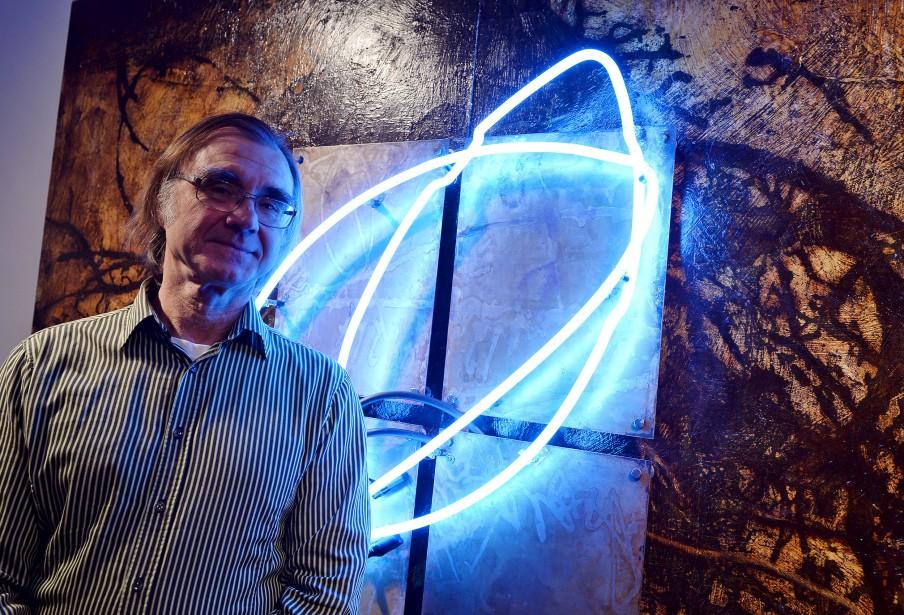 Bill Vincent devant son oeuvre <em>Blue Seed</em> (2004), acrylique sur bois, vernis, acier, néon (Le Soleil, Erick Labbé)