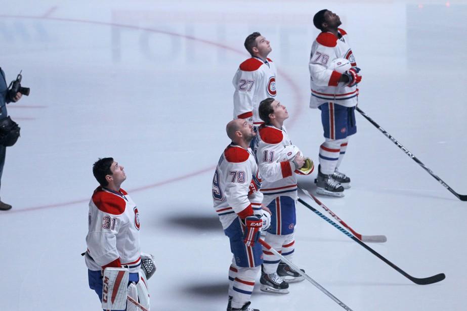 Les Canadiens observent un hommage-vidéo à Jean Béliveau durant une cérémonie d'avant-match auXcel Energy Center. (AP)