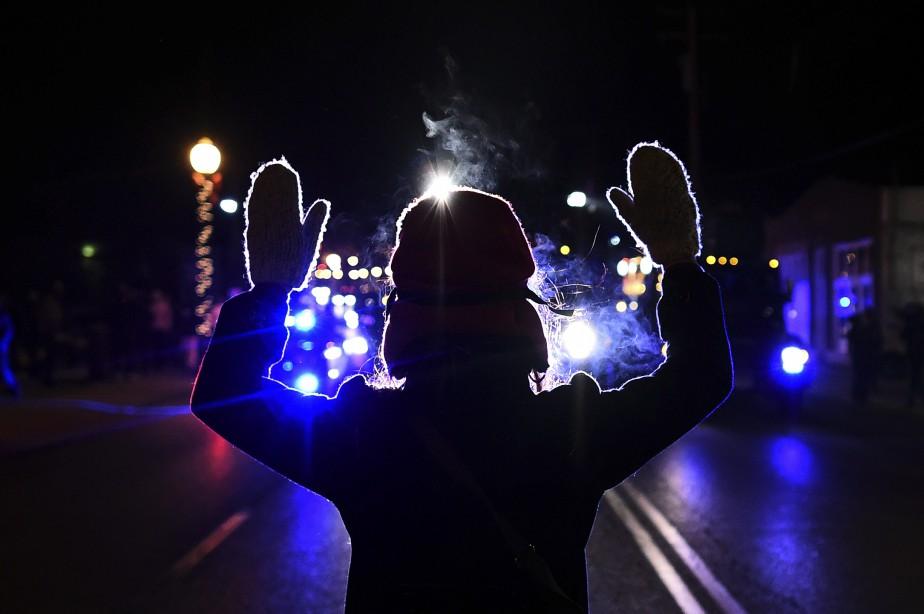 Un manifestant lève les mains devant des voitures de police à Ferguson, au Missouri, la deuxième nuit suivant la décision du jury de ne pas inculper Darren Wilson, le policier qui a abattu Michael Brown. (Agence France-Presse)