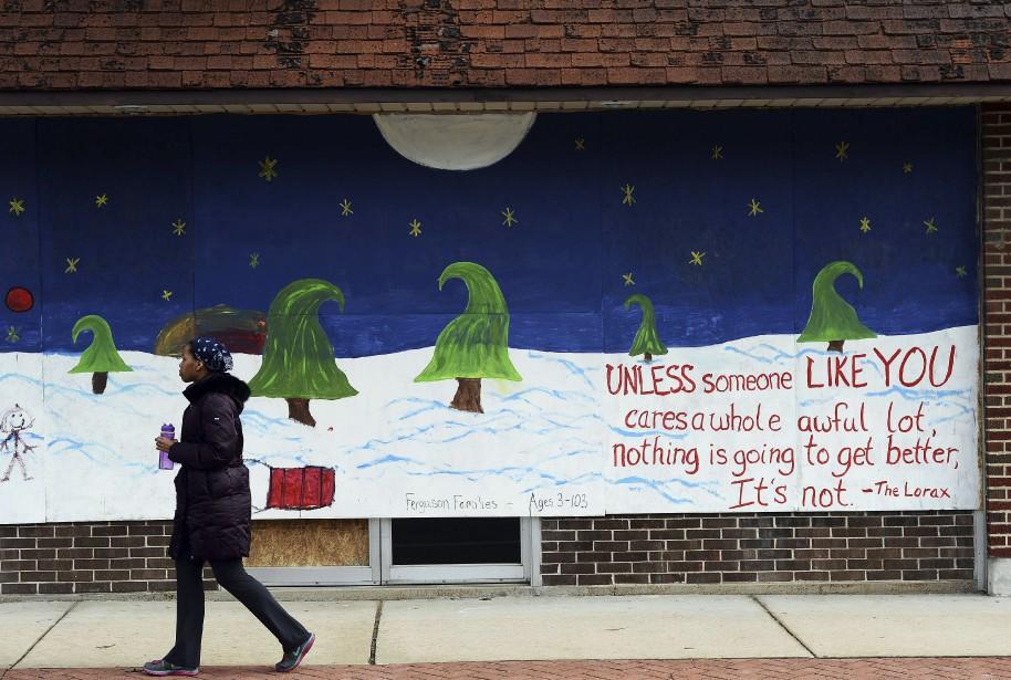 Une femme passe devant une murale qui a été peinturée en hommage à Michael Brown, à Ferguson, au Missouri. Sur la murale, on peut y lire l'inscription suivante : «D'ici à ce que quelqu'un comme toi prenne conscience de la situation, rien ne changera pour le mieux.» (Agence France-Presse)