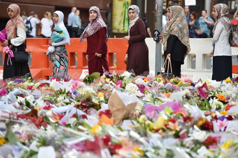 De jeunes musulmanes déposent des gerbes de fleurs... (PHOTO PETER PARKS, AFP)