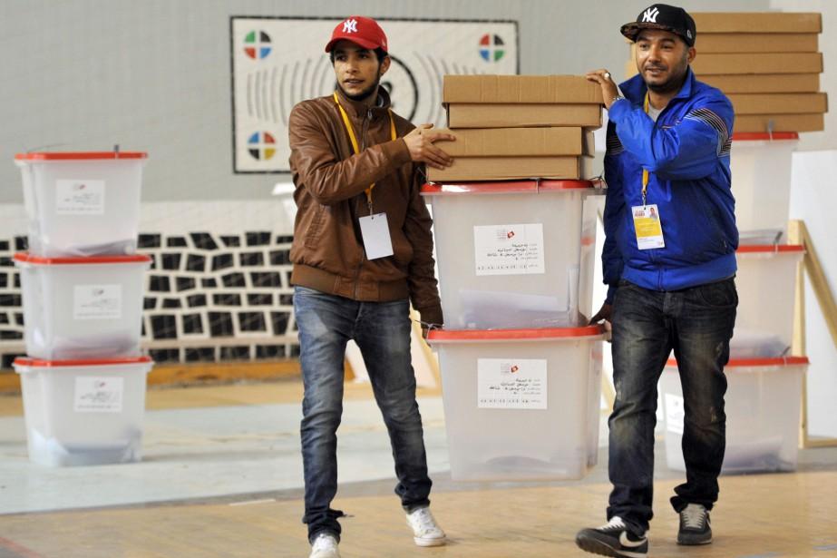 Des employés tunisiens déplacent des boîtes qui contiendront... (PHOTO FETHI BELAID, AFP)